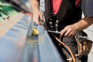 21260945 - close-up of a roofer applying weld into the gutter parts to assemble it